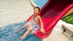 Little boy on water slide at Water County USA