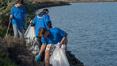 Three people picking up trash by a body of water