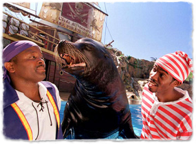 A sea lion interacts with two costumed trainers during a show.