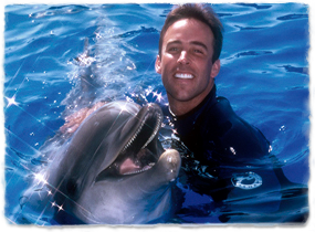 A trainer pets a dolphin while the two pose in the water.