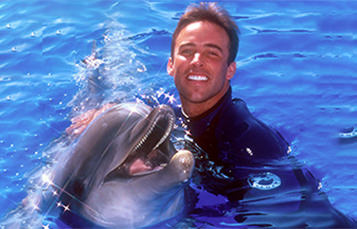 Sea World animal trainer with bottlenose dolphin