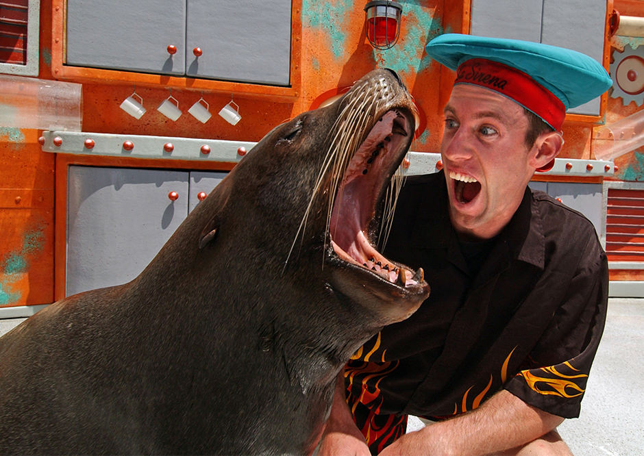 a trainer and sea lion making comedic exaggerated mouth movements