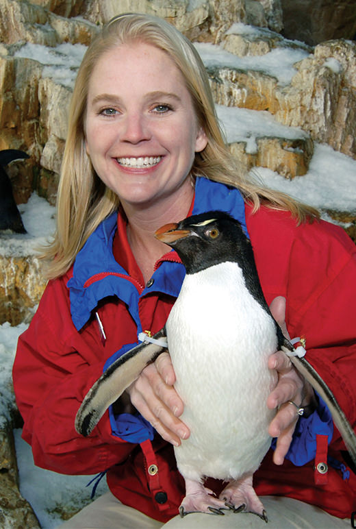 An aviculturist poses with a penguin