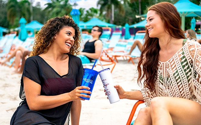 Two women sitting on the beach at Aquatica Orlando