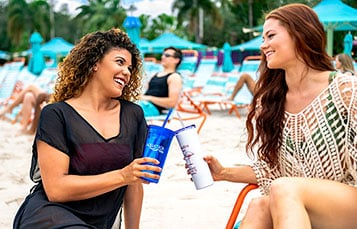 Two women sitting on the beach at Aquatica Orlando water park