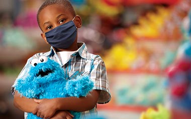 Masked child with a Cookie Monster plush toy
