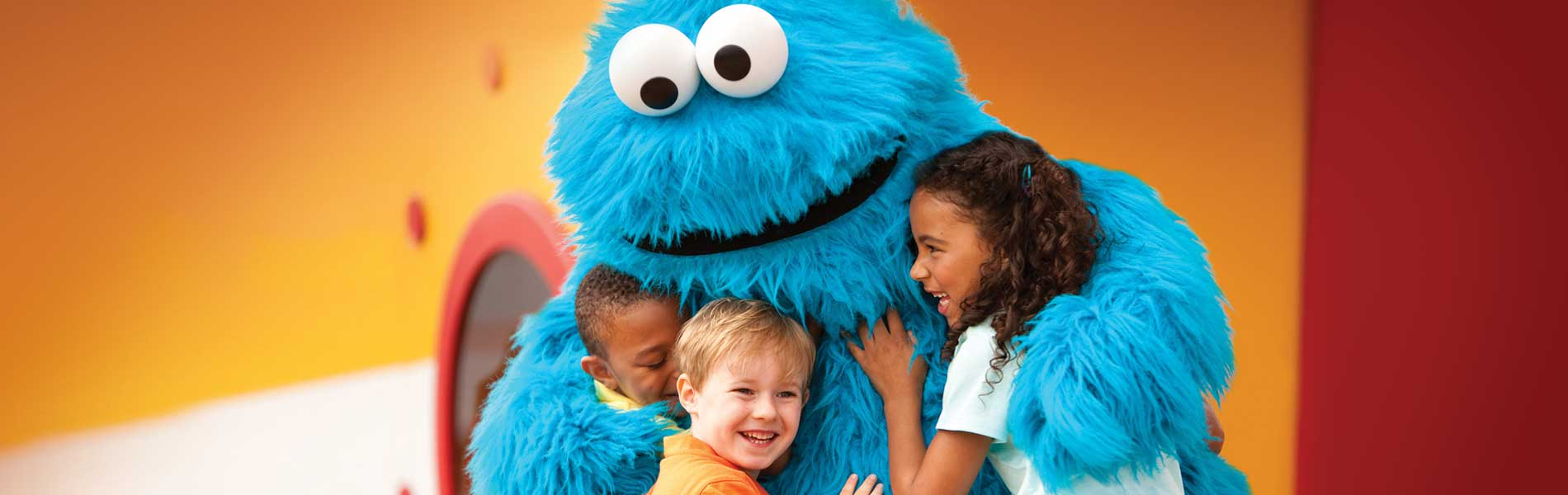 Cookie Monster hugs kids at Sesame Place theme park