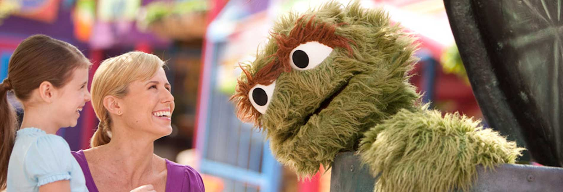 Mother and child laughing with Oscar the Grouch at Sesame Place theme par