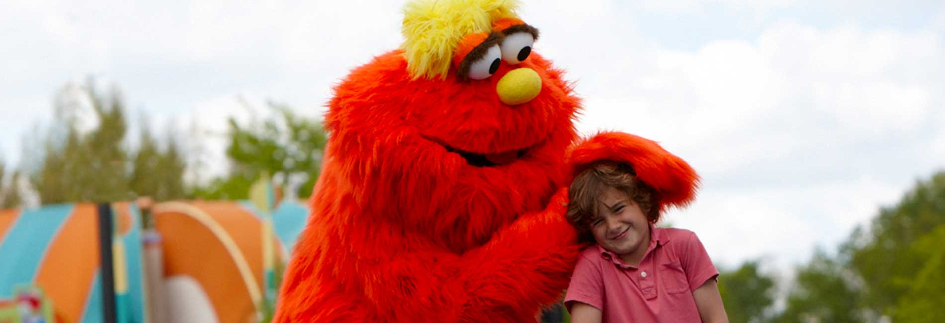 Murray playing with a young boy outside at Sesame Place theme park
