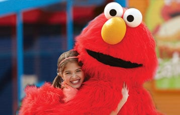 Girl and Elmo hug