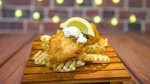 photo of beer battered fish and chips topped with tartar sauce and a lemon