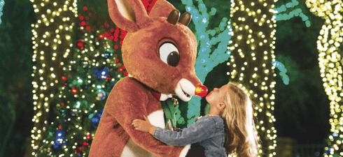 A young girl at Busch Gardens Tampa Bay's Christmas Town gives Rudolph a kiss on the nose.