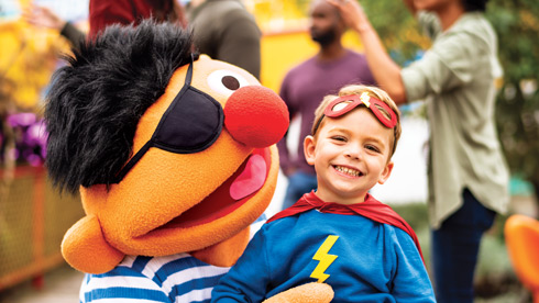 Ernie from Sesame Street dressed in a pirate costume and taking a photo with a young fan dressed as a super hero.