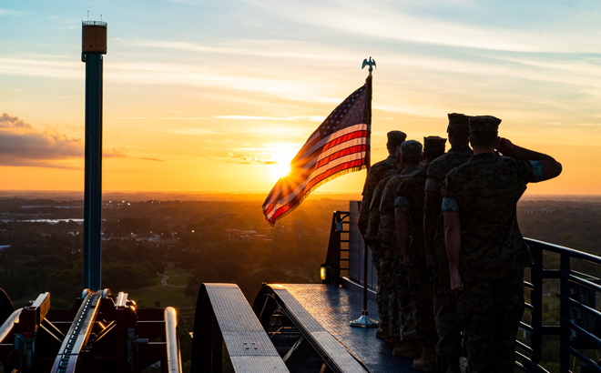 Military Personnel saluting the American Flag on top of Sheikra.