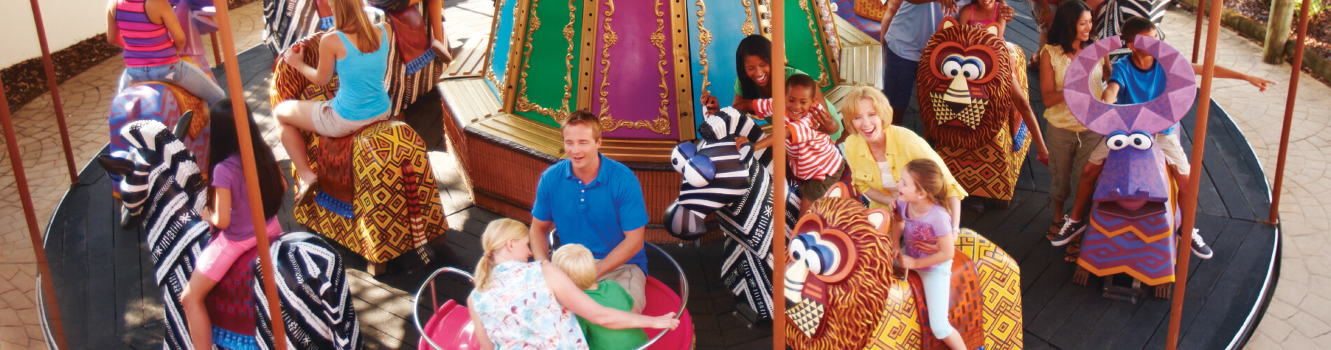 Young kids and parents alike enjoy riding a carousel at Busch Gardens Tampa Bay animal theme park, located in Florida.