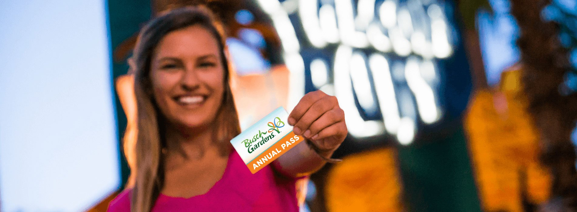 Woman holding up a Busch Gardens Tampa Bay Annual Pass