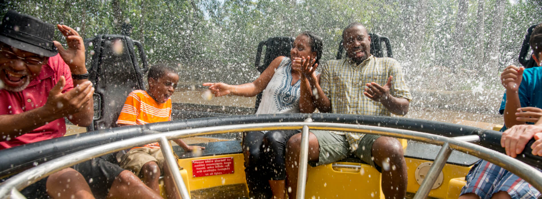 A family feels the water splash onto them as they sit on a yellow and black water ride called Congo River Rapids at Busch Gardens Tampa Bay theme park, located in Florida.