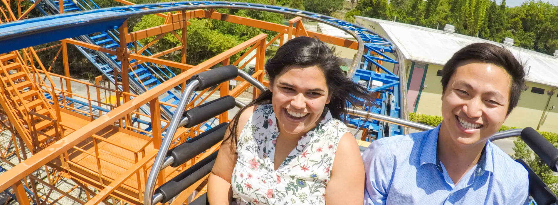 A man and woman smile as they ride a orange and blue ride called Sand Serpent at Busch Gardens Tampa Bay, located in Florida.