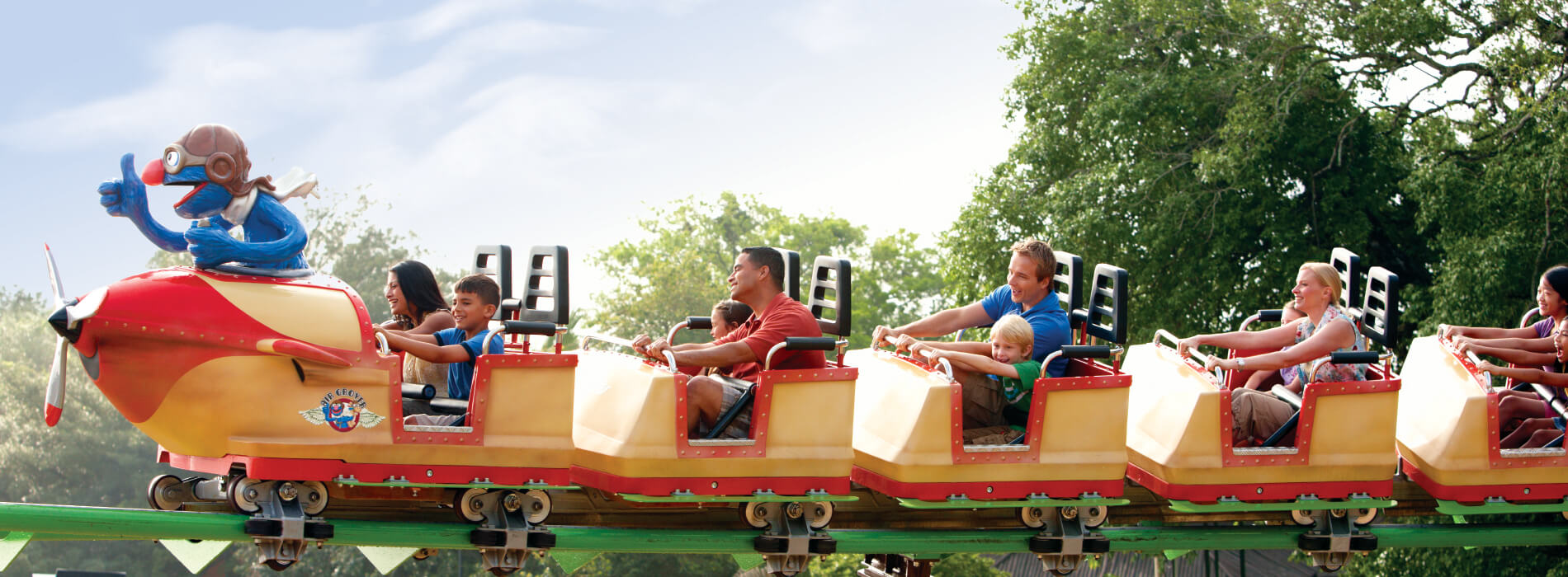 Kids riding a yellow and red roller coaster with adults called Air Grover at Busch Gardens Tampa Bay animal theme park, located in Florida