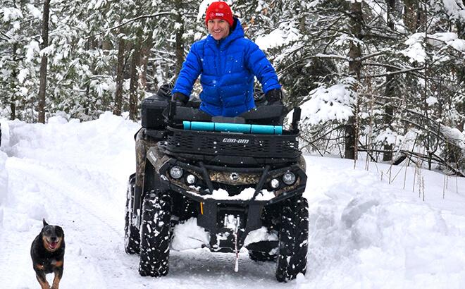 Elvis Stojko on four wheeler in winter with dog