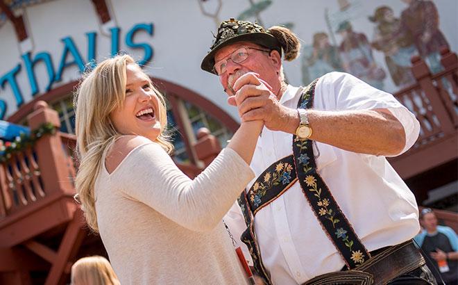 Woman and man wearing lederhosen dancing at Das Festhaus during Busch Gardens Wll Bierfest