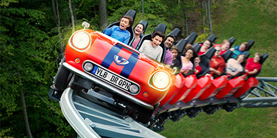 Red train with excited riders of Verbolten roller coaster at Busch Gardens Williamsburg