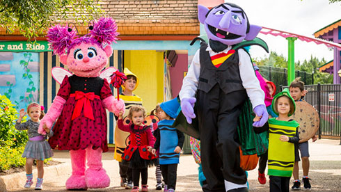 Abby and The Count leading kids around Sesame Street Forest of Fun during the daily costume parade