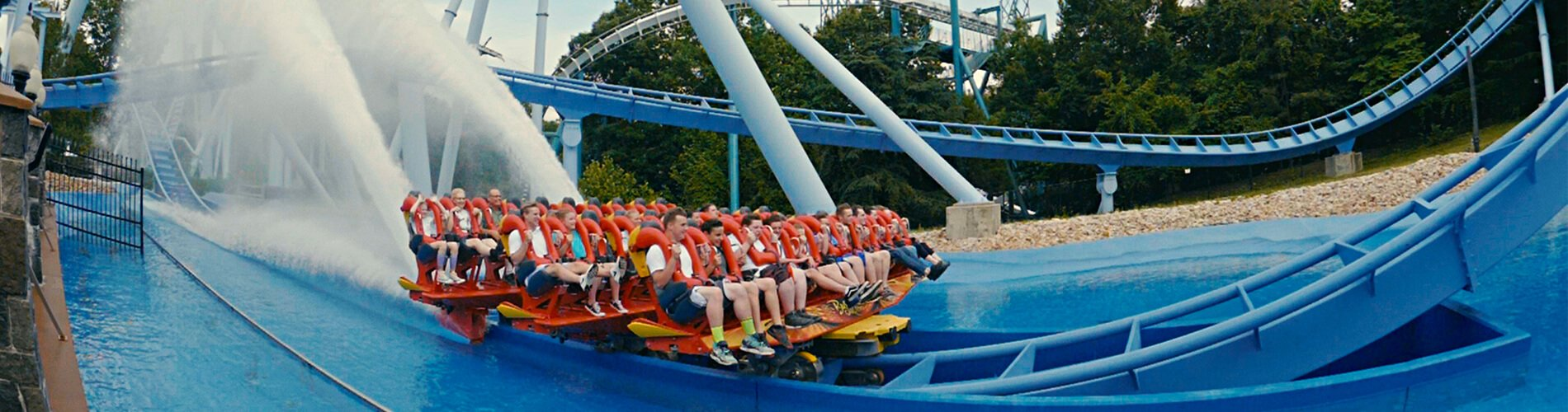 People riding Griffon roller coaster over water