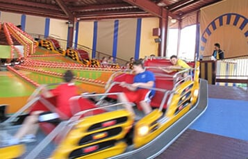 People riding The Trade Wind, a yellow theme park ride at Busch Gardens Williamsburg